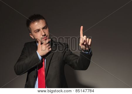 Young business man looking at his finger while thinking of something. He is holding his right hand to his chin.