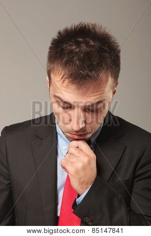 Portrait of a young business man holding his hand to his chin while looking down and thinking of something.