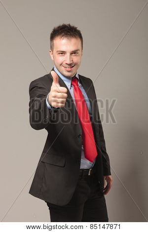 Happy young business man celebrating a succes by showing the thumbs up gesture.