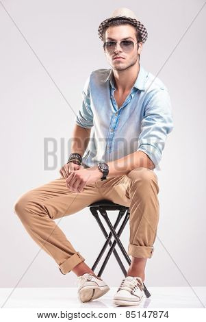 Fashion man sitting on a stool while resting his hands on his leg, looking at the camera