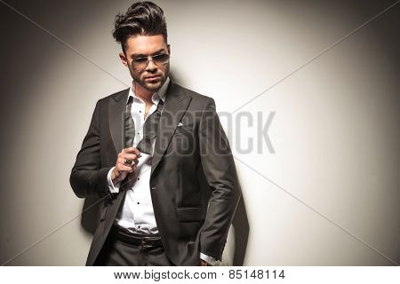 Handsome business man holding his fist up, showing his ring while looking down.