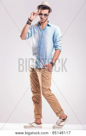 Full length picture of a young casual fashion man taking off his sunglasses while holding one hand in his pocket.