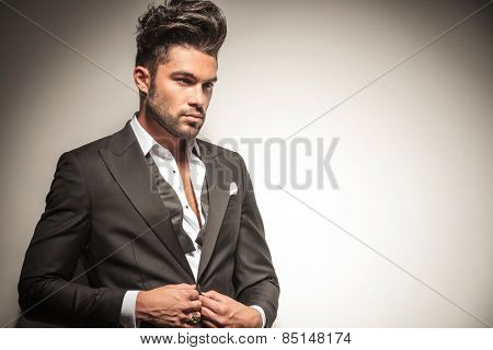 Close up picture of a handsome young business man unbuttoning his jacket while looking away from the camera.