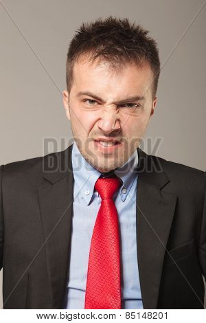 Young business man making a disapproving face, on studio background.