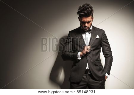Handsome young business man looking down to his ring while holding one hand in his pocket.