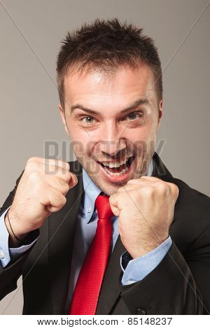Angry business man holding his fists up, getting ready for a fight.