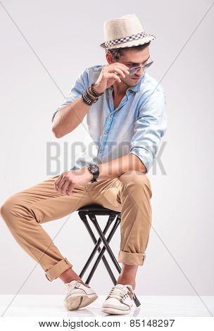 Full body picture of a young casual man sitting on a stool while taking off his sunglasses, looking down.