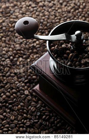 Vintage manual coffee grinder on roasted coffee beans