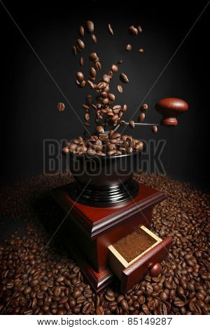 Vintage manual coffee grinder with falling coffee beans