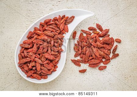dried goji berries in a teardrop shaped bowl against rustic white painted wood