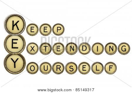 KEY - keep extending yourself - motivation acronym explained in isolated vintage typewriter keys