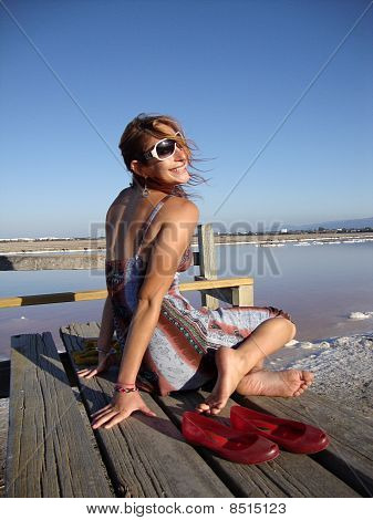 Attractive 20-something Lady Sits On A Pier With Wind Blowing Her Hair In Front Of Purple Salt Mashe