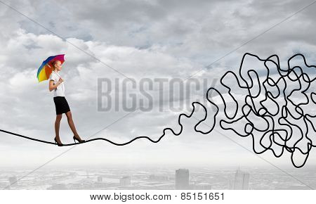 Young businesswoman walking on twisted rope high in sky