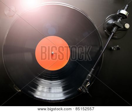 Top view of old fashioned turntable playing a track from black vinyl with a lens flare and instagram look