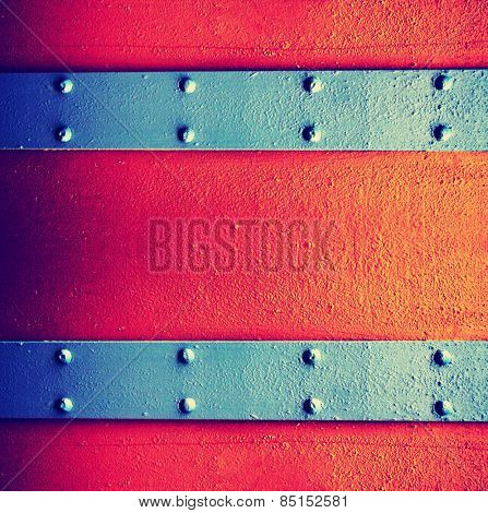 a metal background with a strip of rivets toned with a vintage retro instagram filter effect app or action