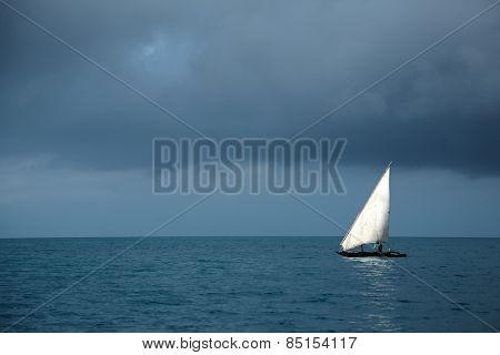 Wooden sailboat (dhow) on water with storm clouds, Zanzibar island