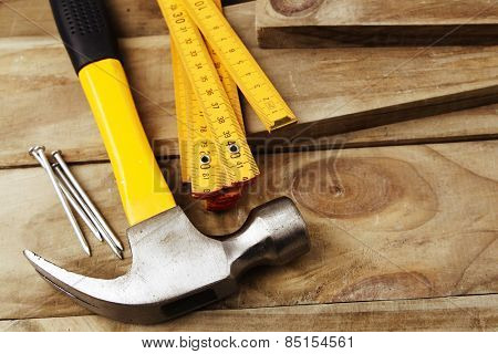Hammer, nails and folding ruler on wood
