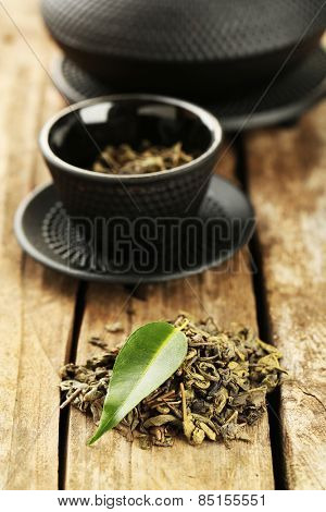 Green tea with leaf on old wooden table