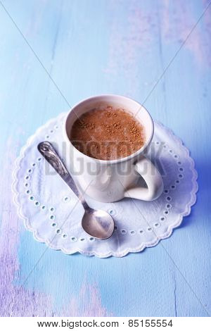 Cup of cocoa with spoon on napkin on wooden background