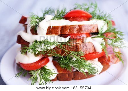 Sandwich with sausage, tomato and mayonnaise on plate, closeup