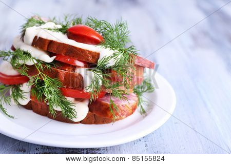 Sandwich with sausage, tomato and mayonnaise on plate on color wooden table background
