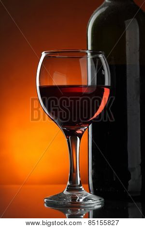 Glass and bottle of red wine over dark red background
