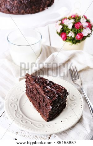 Sliced tasty chocolate cake in plate and glass of milk on table, closeup