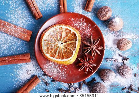 Cinnamon sticks, dried orange, star anise, nutmeg and cloves on color wooden table background