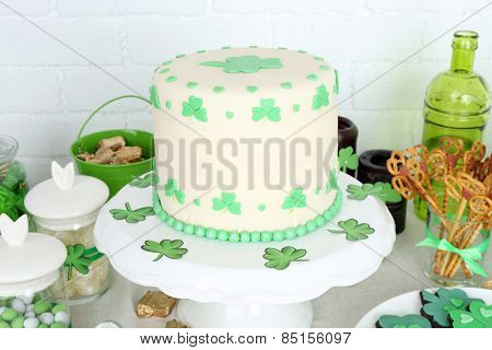 Composition for St Patrick Day with sweets on table on brick wall background