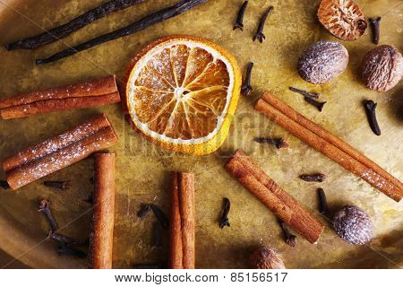 Cinnamon and vanilla sticks, dried orange, nutmeg and cloves on metal tray background