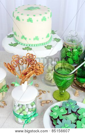Composition for St Patrick Day with sweets and drinks on table on fabric background