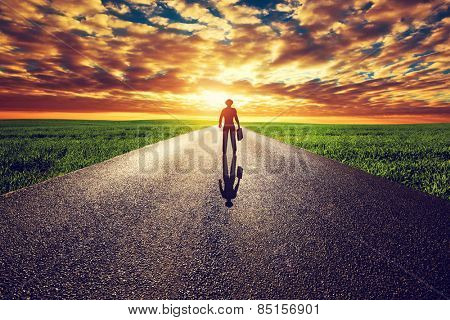 Man with suitcase and hat on long straight road towards sunset sky. Travel, business, destination, adventure concepts.