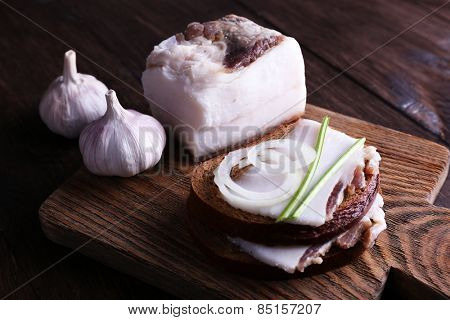Sandwiches with lard and garlic on cutting board on wooden background