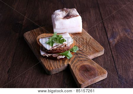 Sandwiches with lard and parsley on cutting board on wooden background
