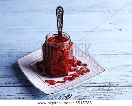 Jar of goji berry jam on plate on wooden background