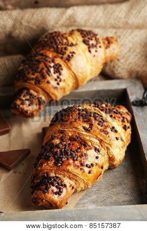 Fresh and tasty croissants with chocolate on wooden tray, on sackcloth background
