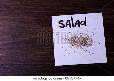 Salad seeds on piece of paper on wooden background