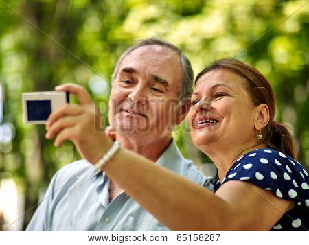 Happy old couple with camera take pictures.