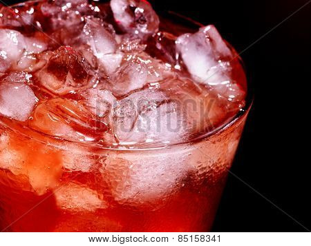Red cube ice of cold drink  with  on dark background. Top view. Close up.