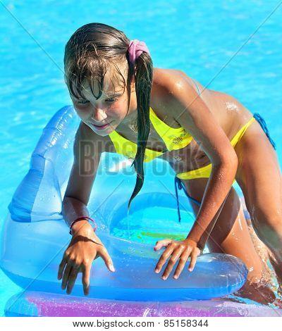 Little girl on inflatable beach mattress.