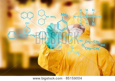 Laboratory man in chemical protective dress drawing chemical formula on foreground