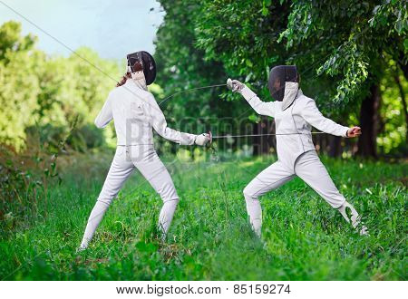 Two rapier fencer women fighting over beautiful nature background