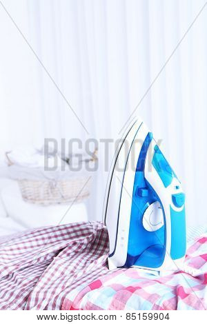 Iron on clothes on ironing board in room