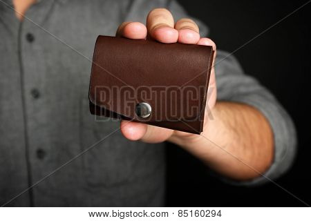 Man holding hand made leather wallet on black background