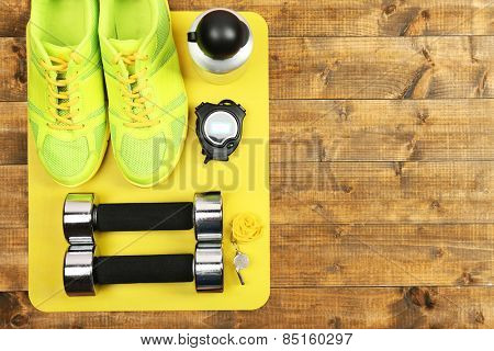 Shoes and sports equipment on mat on wooden floor, top view