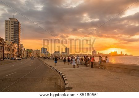 HAVANA,CUBA - MARCH 5, 2014 : Beautiful sunset in Havana with a view of cubans and tourists along the Malecon avenue