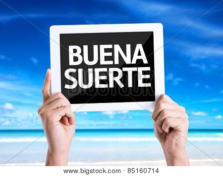 Tablet pc with text Good Luck (in Spanish) with beach background