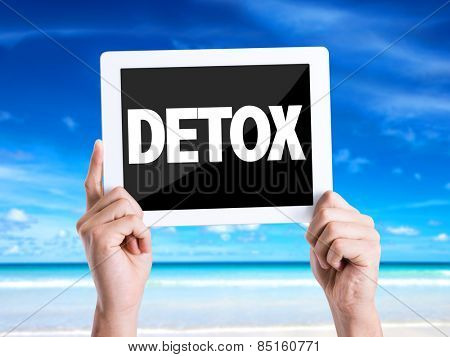 Tablet pc with text Detox with beach background
