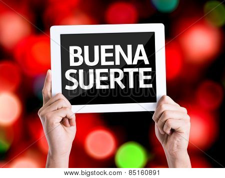 Tablet pc with text Good Luck (in Spanish) with bokeh background