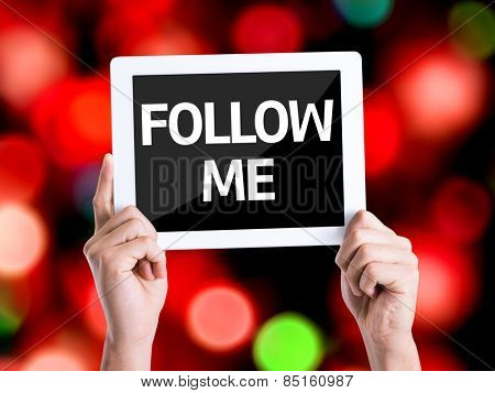 Tablet pc with text Follow Me with bokeh background